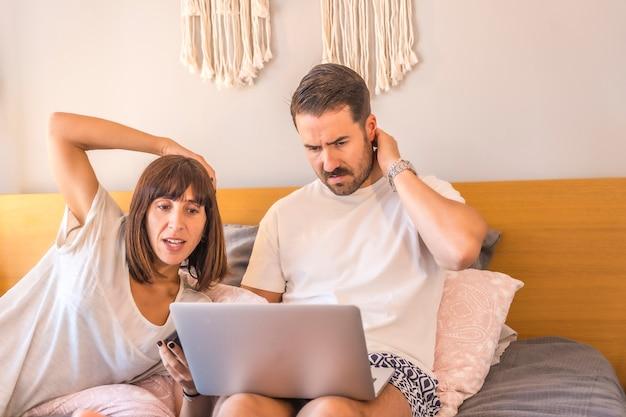 Ein kaukasisches paar auf dem bett mit einem computer und einem telefon, das eine reservierung in einem hotel oder flug vornimmt, urlaub organisiert, neue technologien in der familie. junge fragt sich, welche reise zu wählen