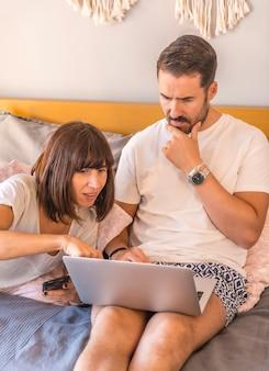 Ein kaukasisches paar auf dem bett mit einem computer und einem telefon, das eine reservierung in einem hotel oder flug vornimmt, urlaub organisiert, neue technologien in der familie. suche nach den besten angeboten