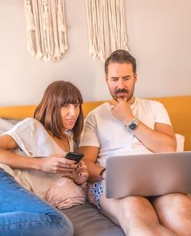 Ein kaukasisches paar auf dem bett mit einem computer und einem telefon, das eine reservierung in einem hotel oder flug vornimmt, urlaub organisiert, neue technologien in der familie.