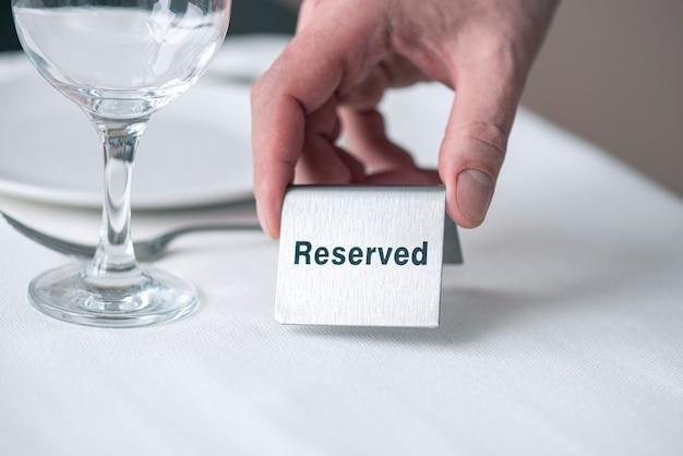 Ein kellner, der eisenschild mit text hält, der auf tisch mit weißer tischdecke am restaurant reserviert wird