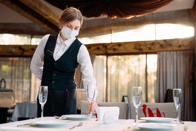 Ein kellner in einer medizinischen schutzmaske serviert den tisch im restaurant.