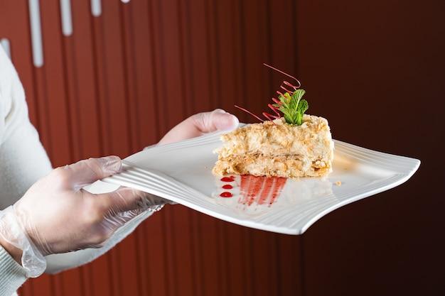Ein kellner in handschuhen hält einen weißen teller napoleon-kuchen in der hand, der mit einer spirale aus roter schokolade, minze und beerenmarmelade verziert ist