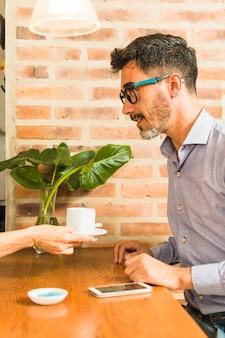 Ein kellner serviert dem mann kaffee, der am tisch sitzt