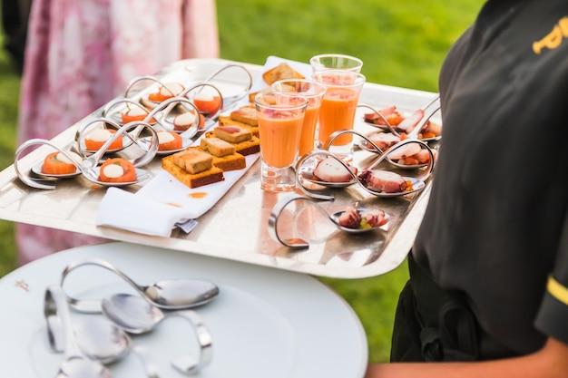 Ein kellner serviert snacks in einem cocktail zur feier einer party. keine gesichter