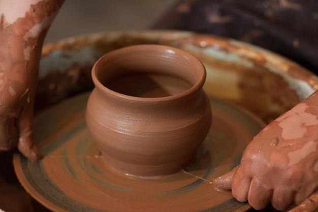 Ein keramiker formt einen tontopf auf einer töpferscheibe eine rotierende töpferscheibe und keramik darauf