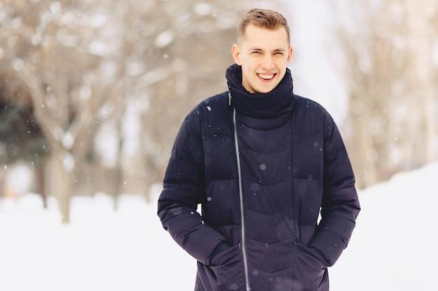 Ein kerl mit hellem kurzen haar in einer winterjacke posiert vor der kamera
