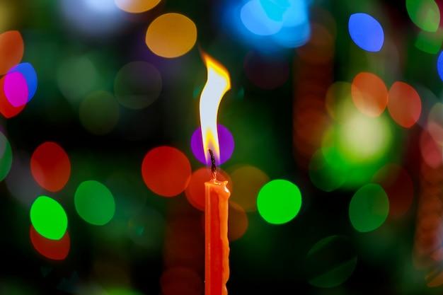 Ein kerzenflammenlicht nachts mit bokeh auf dunklem hintergrund