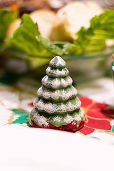 Ein kiefernförmiger salzstreuer mit schnee auf einem tisch mit weihnachtsessen
