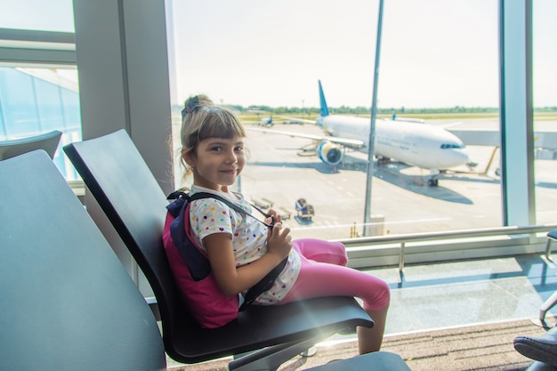 Ein kind am flughafen auf dem hintergrund des flugzeugs