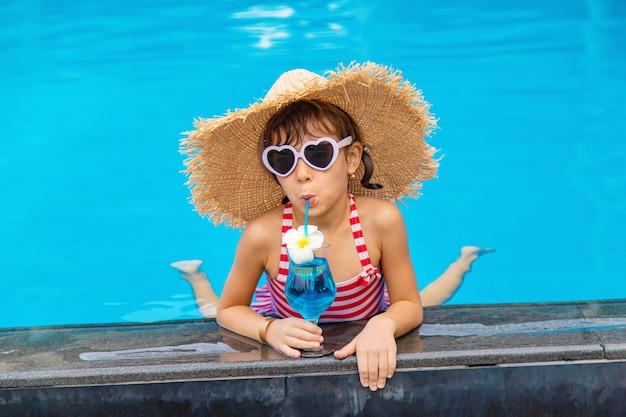 Ein kind am pool trinkt einen cocktail.