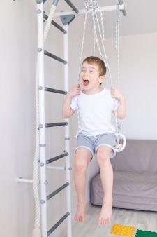 Ein kind an der schwedischen mauer spielt zu hause sport, ein junge klettert mit einem seil auf eine leiter, das konzept von sport und gesundheit