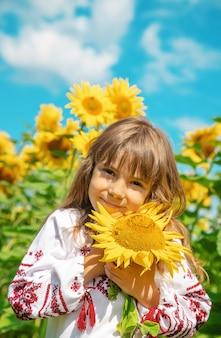 Ein kind auf einem gebiet von sonnenblumen in einem gestickten hemd.
