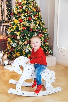Ein kind auf einem hölzernen pferd nahe dem weihnachtsbaum. tiefenschärfe.