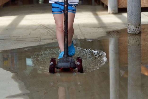 Ein kind auf einem roller fährt durch eine pfütze. radfahren in einer pfütze