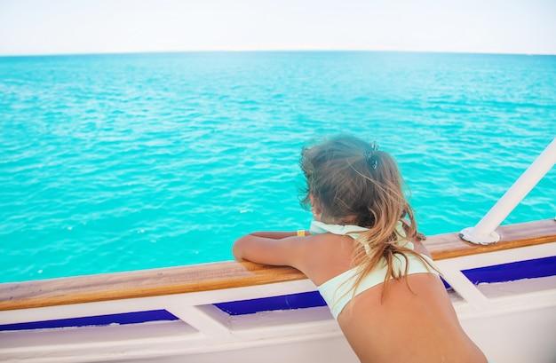 Ein kind auf einer yacht, die das meer segelt.