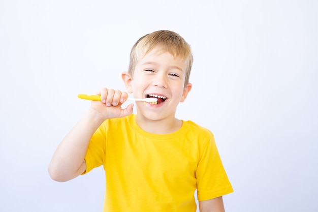 Ein kind auf weißem hintergrund putzt sich die zähne und hält eine zahnbürste in den händen isolieren