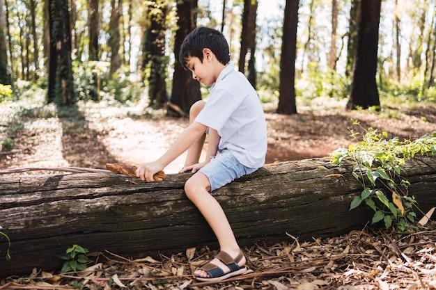 Ein kind, das auf einem gefallenen baumstamm im park sitzt