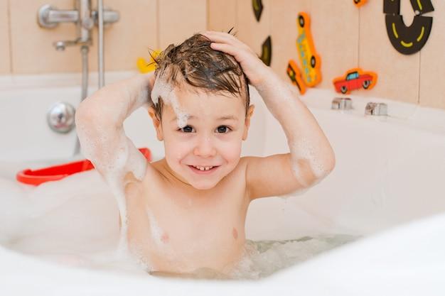 Ein kind, das ein bad mit schaum nimmt