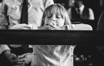 Ein Kind, das in der Kirche betet