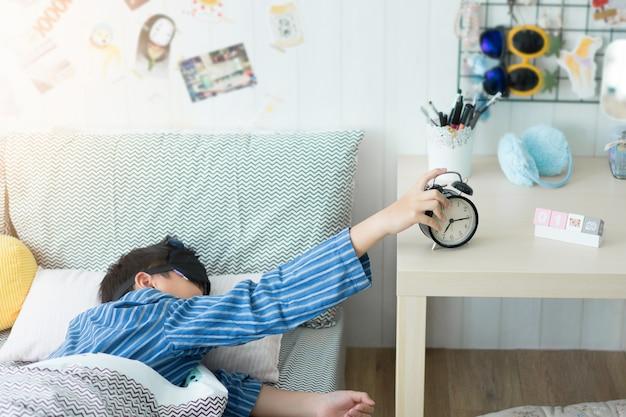 Ein kind, das mit einem wecker im schlafzimmer aufwacht