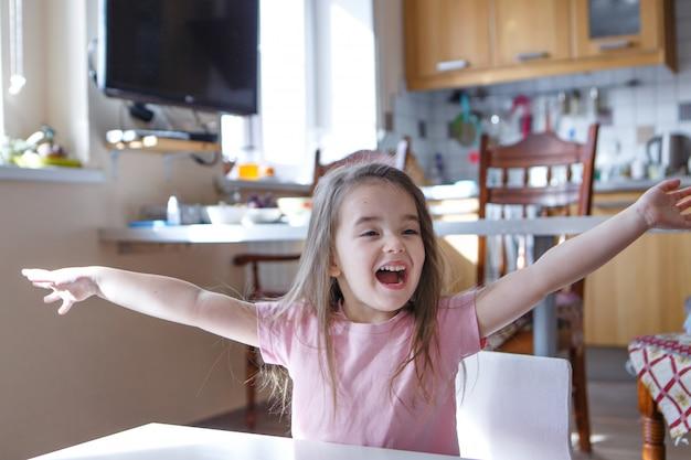 Ein kind, das vor freude schreit. der kleine junge hob die hände. das konzept der meinungsfreiheit von gefühlen, emotionen, ivf, glück