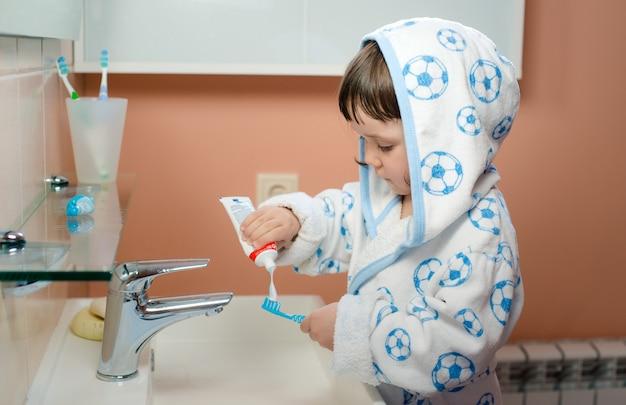 Ein kind des kleinen mädchens putzt zähne im badezimmer. hygiene der mundhöhle.