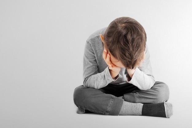 Ein kind, dessen depression auf dem boden sitzt
