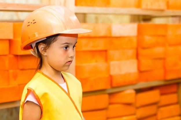 Ein kind, ein mädchen einen helm auf der baustelle eines holzrahmenhauses mit einer zeichnung, eine zeichnung des hauses seine hände