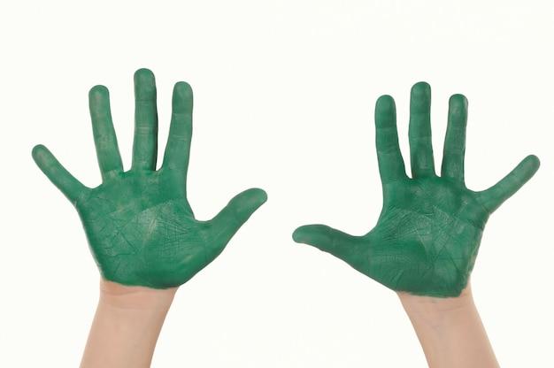 Ein kind gemalt in grünen händen isoliert