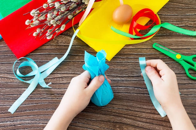 Ein kind hält ein geschenk ein dekoratives ostereier handgemachtes projekt