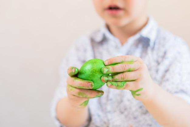 Ein kind hält ein grünes osterei in seinen händen, die mit farbe auf einem weißen hintergrund befleckt werden.