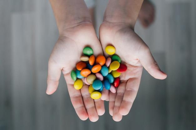 Ein kind hält eine handvoll süßigkeiten