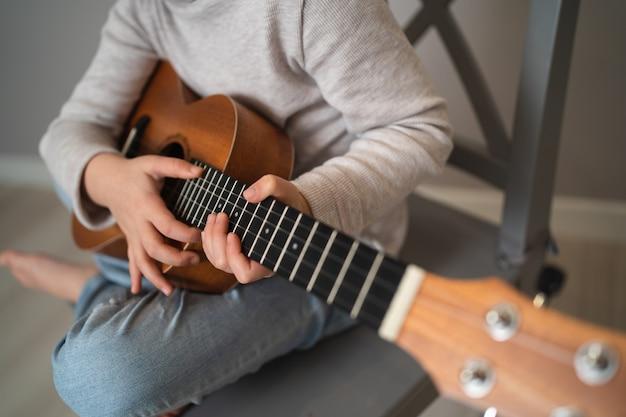 Ein kind hält eine ukulele in den händen. kleine kreative kinder. mädchen lernt online ein instrument zu spielen.