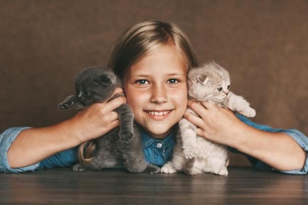 Ein kind hält schöne britische kätzchen in den händen