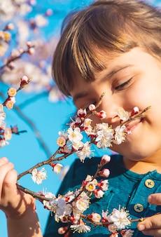 Ein kind im garten blühender bäume. selektiver fokus. natur.