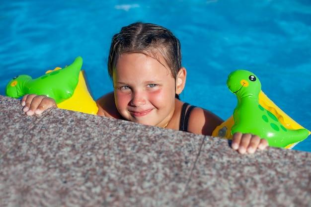 Ein kind im pool, das gesicht eines lächelnden kleinen mädchens, das sich an der seite des pools festhält und ...