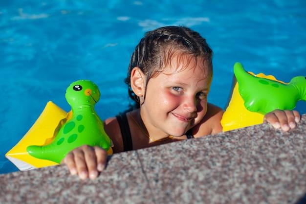 Ein kind in aufblasbaren schwimmflügeln ein fröhliches sechsjähriges mädchen in aufblasbaren schwimmflügeln hat spaß im pool...