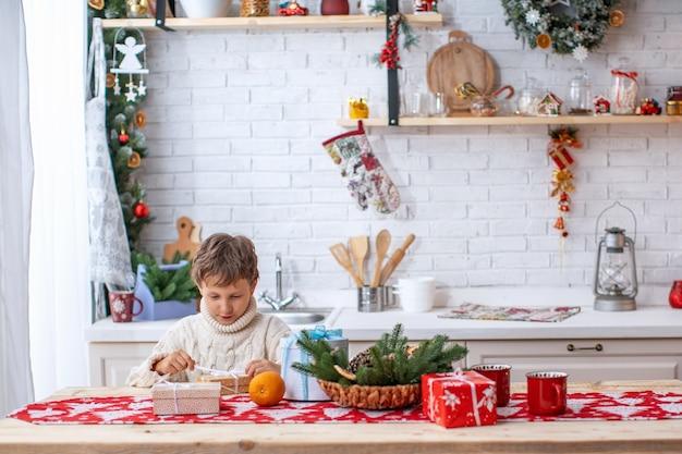 Ein kind in der küche am heiligabend am frühen morgen packt ein geschenk vom weihnachtsmann aus. glücklicher junge auf küchentisch mit geschenkboxen. frohe weihnachten und schöne feiertage!
