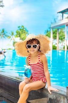 Ein kind in der nähe des pools trinkt einen cocktail. selektiver fokus.