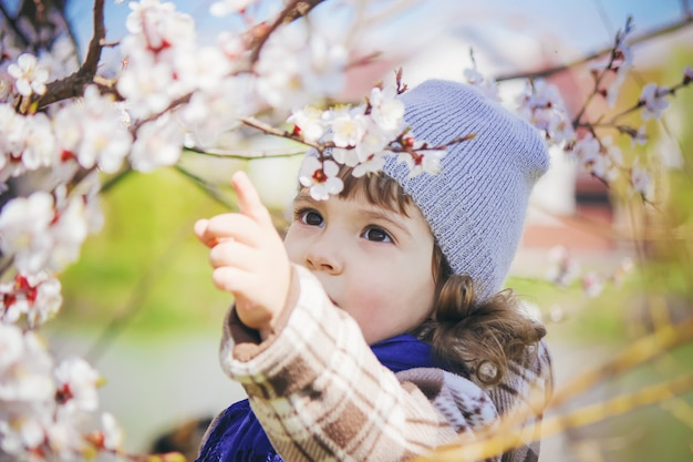 Ein kind in einem blühenden garten. selektiver fokus