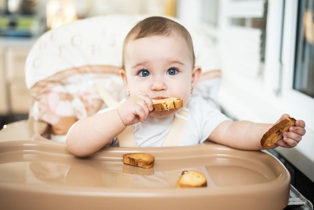 Ein kind in einem hochstuhl isst einen cracker mit rosinen