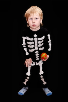 Ein kind in einem skelettkostüm mit einem orangefarbenen ball in der hand schwarzer hintergrund
