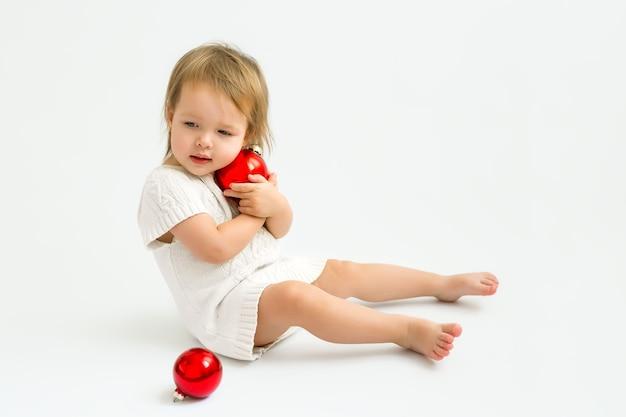 Ein kind in einem strickpullover hält eine weihnachtskugel in den händen und umarmt sie