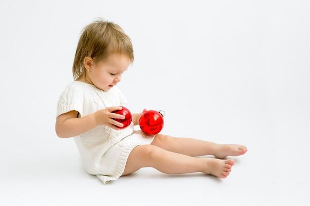 Ein kind in einem strickpullover spielt mit zwei roten weihnachtskugeln aus glas