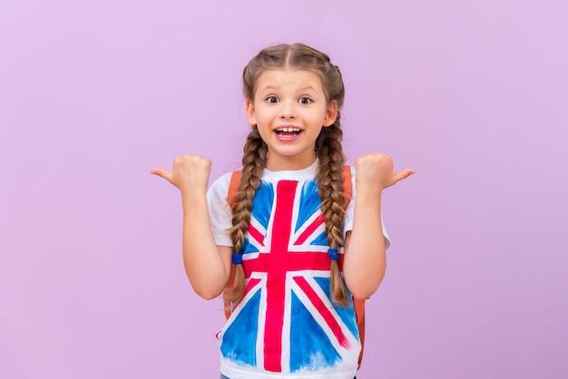 Ein kind in einem t-shirt mit britischer flagge weist auf ihre anzeige hin.