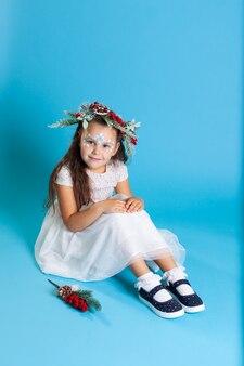 Ein kind in einem weißen schneeflockenkleid und einem schneeblatt-make-up sitzt in blauen schuhen auf dem boden
