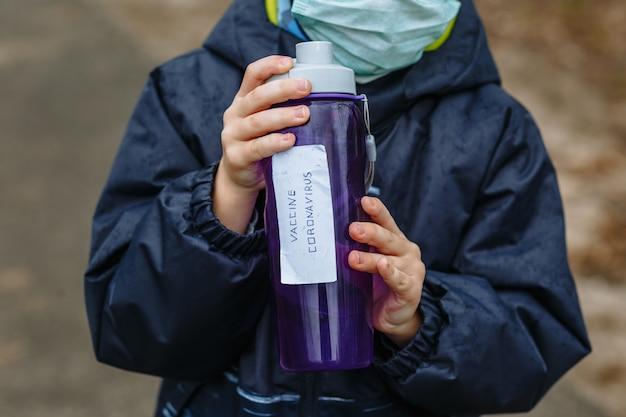Ein kind in einer medizinischen maske hält eine flasche mit dem inschriften-coronavirus-impfstoff