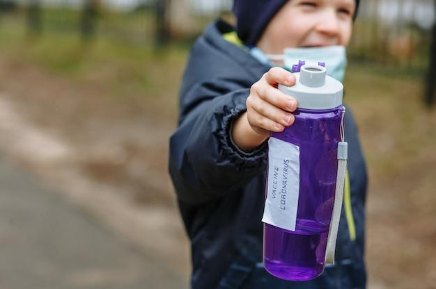 Ein kind in einer medizinischen maske hält eine flasche