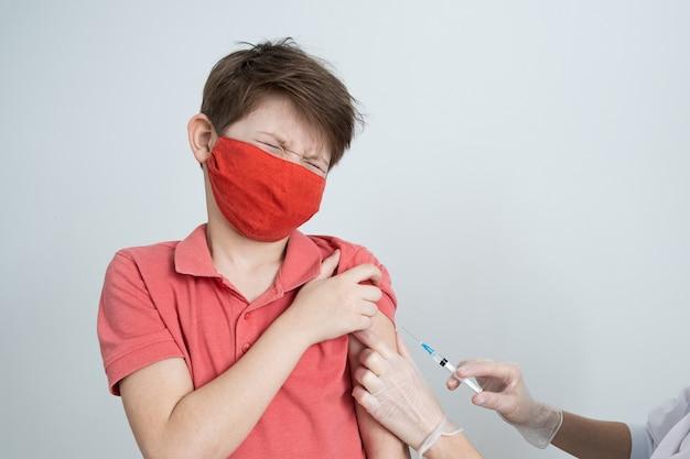 Ein kind in einer medizinischen maske wird bei der covid-pandemie gegen das coronavirus geimpft