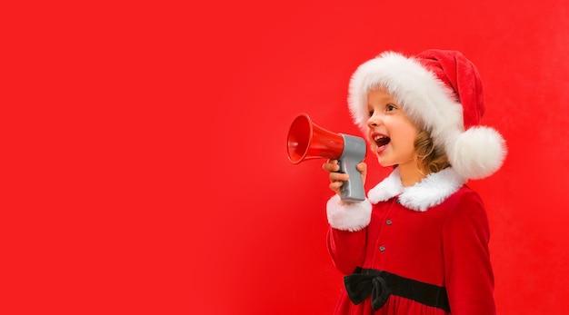 Ein kind in einer roten weihnachtsmütze hält ein megaphon in der hand und schreit slogans zu weihnachten